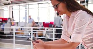 Oficina de In Open Plan de la empresaria usando el teléfono móvil almacen de video