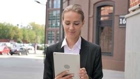 Oficina de Ouside de la mujer que camina y ojeada en la tableta almacen de metraje de vídeo