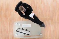 Oficina de Reading Document In del hombre de negocios foto de archivo