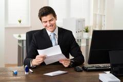 Oficina de Reading Paper In del hombre de negocios imagen de archivo