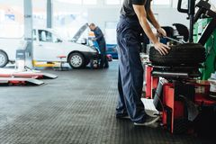 Oficina de reparações do carro com trabalho dos mecânicos fotos de stock
