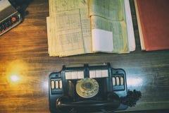 Oficina de trabajo del dise?o: tabla antigua y tel?fono an?logo, l?mpara en la tabla imagen de archivo