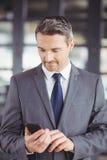 Oficina de Using Cellphone In del hombre de negocios fotografía de archivo libre de regalías
