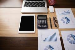 Oficina del escritorio con el ordenador portátil, taplet, pluma, informe del análisis, calculadora Imágenes de archivo libres de regalías