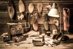 Oficina do sapateiro com ferramentas, sapatas e laços imagem de stock