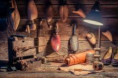 Oficina do sapateiro do vintage com ferramentas, sapatas e laços imagens de stock royalty free