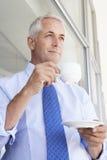 Oficina madura de Standing Outside Modern del hombre de negocios que bebe Coffe Foto de archivo