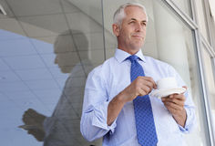 Oficina madura de Standing Outside Modern del hombre de negocios que bebe Coffe Imágenes de archivo libres de regalías