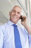 Oficina madura de Standing Outside Modern del hombre de negocios que habla en el teléfono Fotografía de archivo libre de regalías