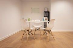 Oficina moderna Muebles fijados con la tabla y las sillas Interior de la oficina minimalista con las paredes blancas, piso de mad imagen de archivo libre de regalías