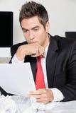 Oficina pensativa de Reading Document In del hombre de negocios imagenes de archivo
