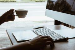 Oficina que trabaja en la tabla de la oficina con el lugar de trabajo de la tabla de la oficina de negocios de la taza del ordena fotografía de archivo