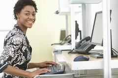 Oficina sonriente de Using Computer In de la empresaria fotografía de archivo libre de regalías