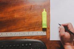 Oficina suply con la pluma de tenencia de la mano en el Libro Blanco con la regla del clip y el teclado de ordenador de madera foto de archivo