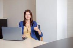 Oficina-trabajador alegre que muestra los pulgares para arriba delante del ordenador portátil Imagen de archivo libre de regalías