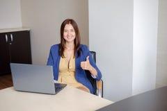 Oficina-trabajador alegre que muestra los pulgares para arriba delante del ordenador portátil Fotos de archivo libres de regalías