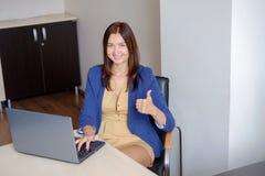 Oficina-trabajador alegre que muestra los pulgares para arriba delante del ordenador portátil Foto de archivo