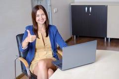 Oficina-trabajador alegre que muestra los pulgares para arriba delante del ordenador portátil Foto de archivo libre de regalías