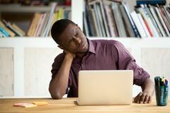 Oficinista afroamericano cansado que sufre de dolor de cuello fotos de archivo