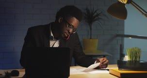 Oficinista afroamericano joven que habla en el teléfono con el jefe, sentándose en oficina moderna tarde en la noche, trabajando  almacen de metraje de vídeo