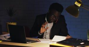 Oficinista afroamericano joven que habla en el tel?fono con el jefe, sent?ndose en oficina moderna tarde en la noche, trabajando  almacen de video
