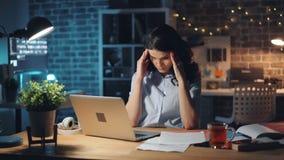 Oficinista agotado que mecanografía en el ordenador portátil entonces que lee dolor de cabeza de la sensación del documento almacen de metraje de vídeo