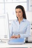 Oficinista bonito en el escritorio Imagen de archivo
