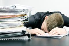 Oficinista cansado y una pila de documentos imagen de archivo