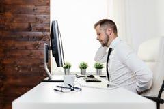 Oficinista con dolor de sentarse en el escritorio todo el día imagen de archivo libre de regalías