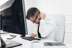Oficinista con dolor de sentarse en el escritorio todo el día foto de archivo libre de regalías