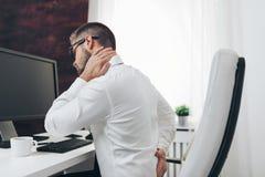 Oficinista con dolor de sentarse en el escritorio todo el día fotos de archivo