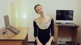 Oficinista de sexo femenino bastante joven con un cuello largo que estira y que sonríe almacen de metraje de vídeo