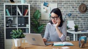 Oficinista de sexo femenino que habla en el teléfono móvil y que usa el ordenador portátil entonces que toma notas almacen de video