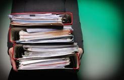 Oficinista de sexo femenino que lleva una pila de ficheros Imágenes de archivo libres de regalías