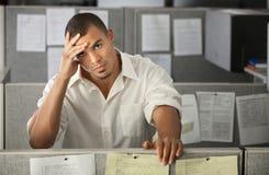 Oficinista de sexo masculino con exceso de trabajo Imágenes de archivo libres de regalías