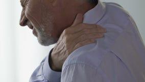 Oficinista de sexo masculino en sus 50 que sufren del dolor de espalda debido a la forma de vida sedentaria almacen de metraje de vídeo