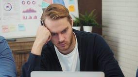 Oficinista de sexo masculino pensativo que mira la pantalla de ordenador con datos almacen de metraje de vídeo