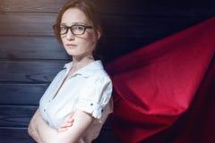 Oficinista del Superwoman que se coloca en un traje y una capa roja Fotos de archivo