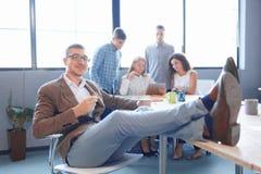 Oficinista descarado con las piernas en la tabla en el fondo borroso Concepto de la dirección imagenes de archivo
