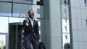 Oficinista emocionado que muestra sí el gesto, hombre joven afortunado que celebra progreso metrajes
