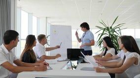 Oficinista en demostraciones de la reunión del negocio del diagrama en Whiteboard para los colegas en la sala de reunión metrajes