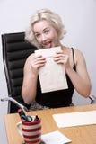 Oficinista en el escritorio que lame un sobre Imagenes de archivo