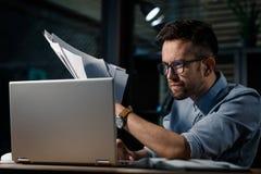 Oficinista enfocado que usa el ordenador portátil imágenes de archivo libres de regalías