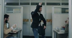 Oficinista feliz del baile que viene en la oficina, todos los colegas que sientan en ellos el escritorio del trabajo y la mirada  almacen de metraje de vídeo