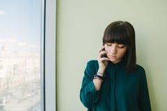 Oficinista hermoso joven de la mujer que habla en el teléfono en la ventana y las miradas abajo foto de archivo