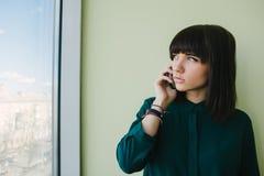 Oficinista hermoso joven de la mujer que habla en el teléfono y que mira en la ventana Imagenes de archivo