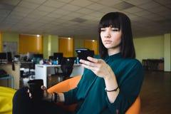 Oficinista hermoso joven en una oficina moderna en trabajos de fondo Mujer de negocios que sostiene una taza de café Trabajo de l Imágenes de archivo libres de regalías