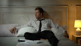 Oficinista joven que se sienta en la cama, frustrada con la terminación del empleo almacen de video