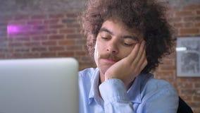 Oficinista nerdy aburrido que mecanografía en el ordenador portátil y que se sienta en la oficina moderna, intentando no dormir d