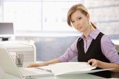 Oficinista que hace papeleo en el escritorio Foto de archivo libre de regalías
